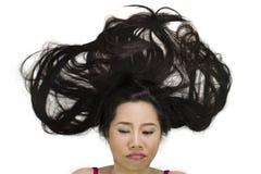 Closeupstående av lynniga asiatiska kvinnor som ligger på jordning med svart långt hår agera som är upprivet, olyckligt royaltyfri fotografi