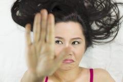 Closeupstående av lynniga asiatiska kvinnor som ligger på jordning med svart långt hår agera som är upprivet, olyckligt arkivfoto