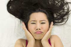 Closeupstående av lynniga asiatiska kvinnor som ligger på jordning med svart långt hår agera som är upprivet, olyckligt arkivbilder