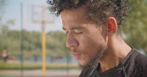 Closeupstående av manliga basketspelaren för ung stilig afrikansk amerikan som den är bestämt sitta utomhus arkivfilmer