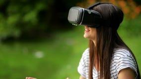 Closeupstående av unga flickan med mörkt långt hår genom att använda mobila Apps med innovativt faktiskt teknologisammanträde när arkivfilmer
