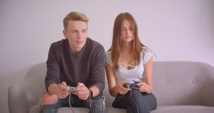 Closeupstående av unga gulliga caucasian gamerpar som spelar videospel som tillsammans inomhus sitter på soffan i lager videofilmer