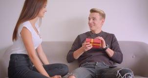 Closeupstående av unga gulliga caucasian par inomhus hemma Man som använder telefonen som sitter på soffan och motta arkivfilmer