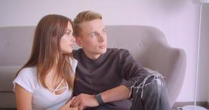 Closeupstående av unga gulliga caucasian par som är mjukt och förälskat sammanträde som tillsammans inomhus kopplas av i stock video