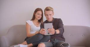 Closeupstående av unga gulliga caucasian par som har en video appell på minnestavlan som tillsammans inomhus sitter på soffan stock video