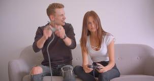 Closeupstående av unga gulliga caucasian par som spelar videospel som tillsammans inomhus sitter på soffan i arkivfilmer