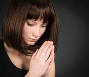 Closeupstående av ungt be för brunettkvinna Be flickan på mörk bakgrund Arkivfoton