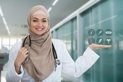 Closeupstående av vänskapsmatchen som ler hållande medicinska symboler för säker muslimsk kvinnlig doktor Royaltyfri Bild