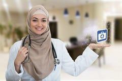 Closeupstående av vänskapsmatchen som ler hållande medicinska symboler för säker muslimsk kvinnlig doktor Arkivfoto
