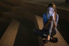 Closeupstående som ler eller skrattar den unga freelancerkvinnan som ser telefonen som ser goda nyheter eller foto med trevlig si Arkivbild