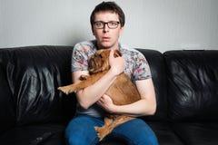 Closeupstående, ung man som sitter på den svarta lädersoffan med den röda hunden, hållande ögonen på TV som förvånas på vad han s arkivbild