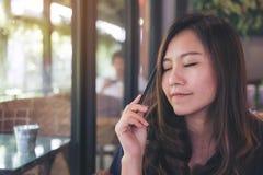 Closeupståendebild av en härlig asiatisk kvinna som stänger henne ögon och sitter i modernt kafé, medan tänka om affär arkivfoto