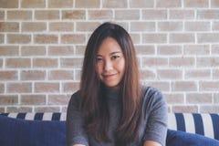 Closeupståendebilden av en härlig asiatisk kvinna med smileyframsidasammanträde på soffan med mening bra och kopplar av med tegel arkivbild