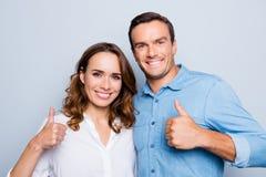 Closeupståenden av att le par som gör en gest tummar, up anseende arkivfoto