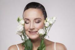 Closeupståenden av den gladlynta härliga kvinnan med perfekt hud och åldriga skrynklor är lutar på blommor Begrepp för hudomsorg  royaltyfri bild