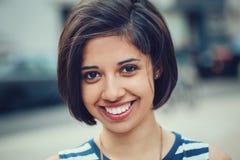 Closeupståenden av den härliga le unga latinska latinamerikanska flickakvinnan med kort mörkt svart hår guppar arkivfoto