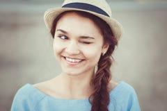 Closeupståenden av den roliga härliga le vita Caucasian brunettflickan som blinkar, i blått, klär och sugrörhatt Arkivfoto