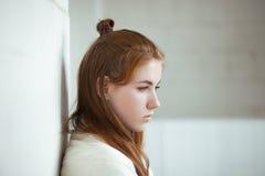 Closeupståenden av den unga förtjusande rödhårig mankvinnan som sloggs in i en vit, stack filten som poserar nära inomhus naturli fotografering för bildbyråer