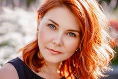 Closeupståenden av mitt åldrades den vita caucasian kvinnan med vinkat lockigt rött hår med blåa ögon royaltyfri foto