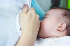 Closeupståenden av modern som ammar hennes nyfött, behandla som ett barn med b Royaltyfri Bild