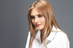 Closeupst?ende av en ung h?rlig blond kvinna i en vit skjorta royaltyfria foton