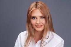Closeupst?ende av en ung h?rlig blond kvinna i en vit skjorta royaltyfri foto