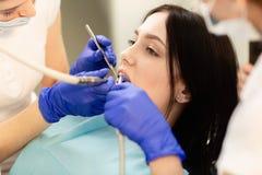 Closeupst?ende av patienten f?r ung kvinna som sitter i tandl?karestol Doktorn unders?ker t?nderna Tand- v?rd- f?rhindrande royaltyfria foton