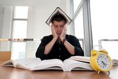 Closeupstående av vita mannen som omges av högar av böcker, ringklocka som är stressad från projektstopptiden, studie, examina Arkivbild