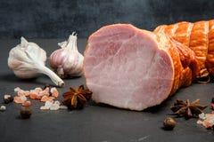 Closeupstora biten av rökt saltad och rökt skinka med saltar, kryddor och vitlök två royaltyfri fotografi