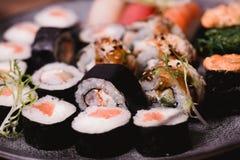 Closeupsushinigirien och rullar tjänade som på den bruna trätabellen i platta sund asiatisk mat stort vatten för fotografi för ma Royaltyfria Bilder