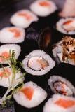 Closeupsushinigirien och rullar tjänade som på den bruna trätabellen i platta sund asiatisk mat stort vatten för fotografi för ma Arkivfoton