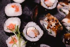 Closeupsushinigirien och rullar tjänade som på den bruna trätabellen i platta sund asiatisk mat stort vatten för fotografi för ma Royaltyfri Foto