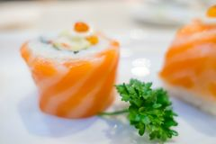 Closeupsushirulle med den nya laxen i den vita plattan Japanen utformar mat Arkivbilder