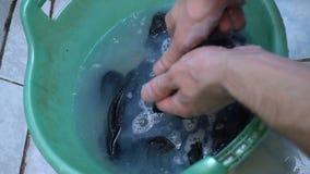 Closeuptvagningsocka i handfat vid handen händer för man` s, tvättande sockor begrepp av ensamma män arkivfilmer
