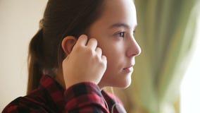 Closeupultrarapidlängd i fot räknat av den ledsna tonårs- flickan som sätter hörlurar i öron och ser ut ur fönster stock video