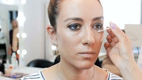 Closeupultrarapidvideo av den yrkesm?ssiga makeupkonstn?ren som arbetar med modellen i anletestudio applicera sk?nhetsmedelkvinna lager videofilmer