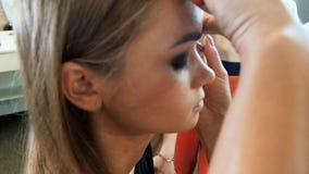 Closeupultrarapidvideo av den yrkesm?ssiga makeupkonstn?ren som arbetar med modellen i anletestudio applicera sk?nhetsmedelkvinna arkivfilmer