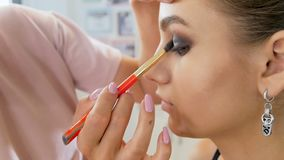 Closeupultrarapidvideo av den yrkesm?ssiga makeupkonstn?ren som arbetar med modellen i anletestudio applicera sk?nhetsmedelkvinna stock video