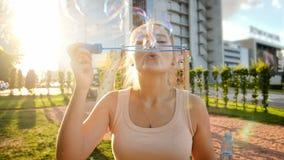 Closeupultrarapidvideoen av den härliga le unga kvinnan som blåser såpbubblor parkerar in, på solnedgången arkivfilmer