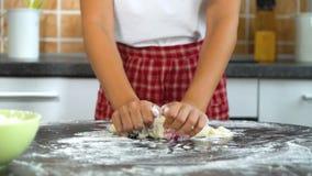 Closeupunga flickan räcker att knåda deg på den mörka tabellen i kök lager videofilmer