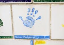Closeupvägg av tegelplattor som göras av barn, framdel av den nationella minnesmärken för oklahoma city & museum, med blommor i f Royaltyfri Foto