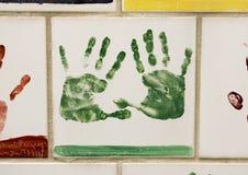 Closeupvägg av tegelplattor som göras av barn, framdel av den nationella minnesmärken för oklahoma city & museum, med blommor i f royaltyfria bilder