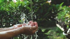 Closeupvattenflöde till handen av kvinnor för naturbegrepp på gummina Royaltyfria Bilder