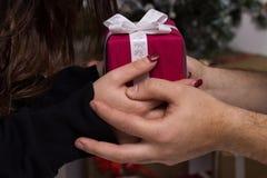 Closeview des mains de l'homme donnant le cadeau rouge de Noël Images stock