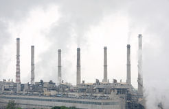 Closeview of thermal power chimneys with smokes. Dense pollluted smokes and haze surrounding the thermal power Stock Image