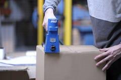 Closing a box with stiching machine stock image