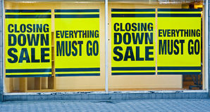 Closing down: effects of recession. A macro image of a shop window pasted with 'closing sale down' notices and ' everything must go ' . In the recession stock photo