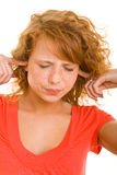 Closing the ears. Young redhaired woman closing her ears Royalty Free Stock Photos