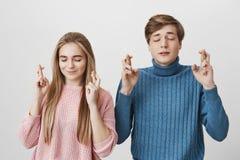 Closing femenino y masculino joven sus ojos que cruzan los fingeres con esperanza mientras que anticipa las noticias importantes  Foto de archivo libre de regalías