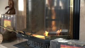 Closing the fireplace with glass lid. We see a process of making the briquettes out of wood and using them to blaze up the fire in fireplace stock video